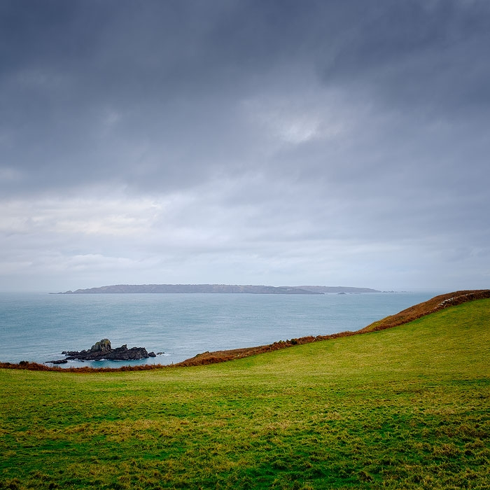 View across a Herm field looking toward Sark on a stormy day.