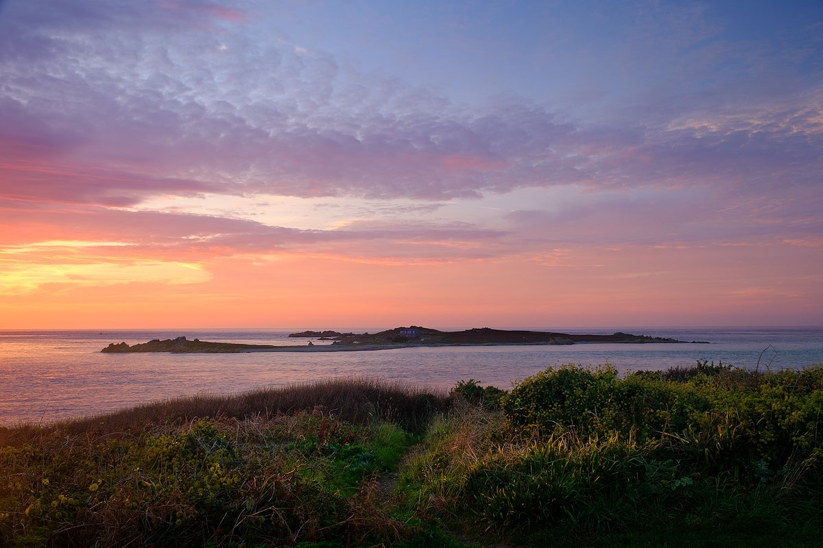 Beautiful coloured clouds at sunset overlooking Lihou Island, Guernsey, viewed from L'Eree headland.