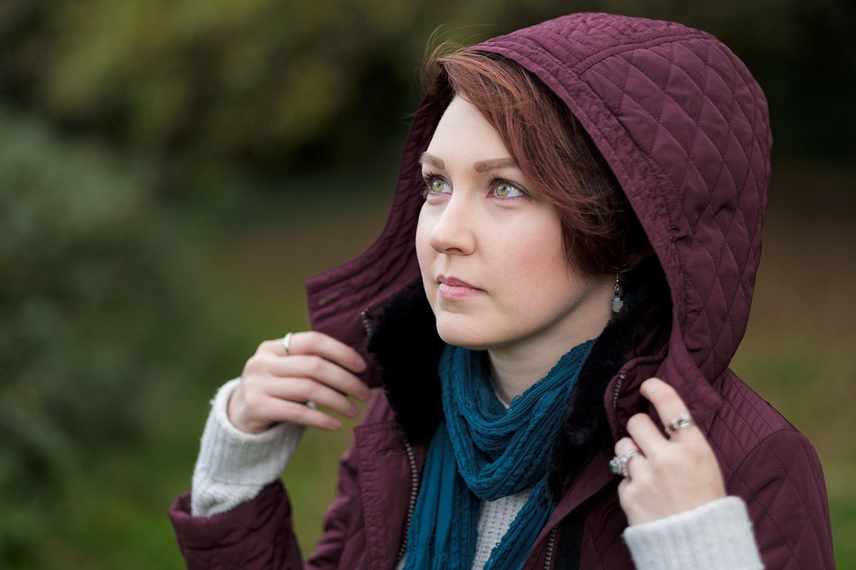 Portrait of a young woman with green eyes & red hair wearing a burgundy hood looking away from camera.